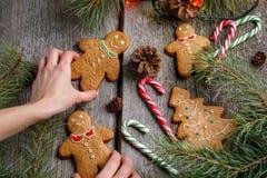 女孩装饰圣诞节的一张桌 姜饼人 姜饼干和棒棒糖在圣诞节桌上 美丽的克里斯 免版税库存照片