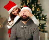 女孩覆盖物注视她的惊奇的男朋友在圣诞节 库存图片