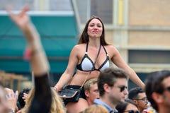 女孩观看一个音乐会坐她的男朋友肩膀  免版税库存照片