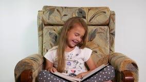 女孩观看与照片的一个册页并且笑 股票视频