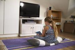 女孩观看电视和使用数字式片剂在游戏室 库存图片