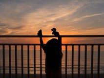 女孩观看的日出的剪影 免版税图库摄影