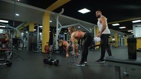 女孩解决在与教练的健身房 股票视频