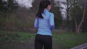 女孩训练户外 遗弃情人的 蓝色体育衣裳的一个女孩沿晚上公园跑 回到视图 女性 影视素材