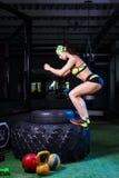 女孩训练她的在跳在一个大轮胎的健身房的腿的肌肉 概念体操生活方式人体育运动 库存图片