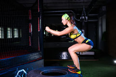 女孩训练她的在跳在一个大轮胎的健身房的腿的肌肉 概念体操生活方式人体育运动 免版税库存照片
