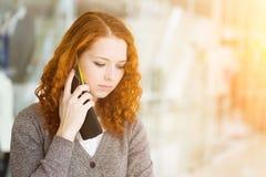 女孩讲话由电话。 免版税库存图片