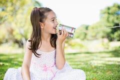 女孩讲话通过锡罐电话 免版税库存照片