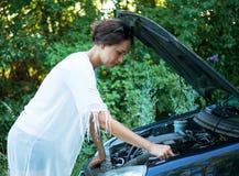 女孩设法修理一辆残破的汽车 库存照片