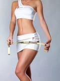 女孩评定与一个评定的磁带的大腿 免版税图库摄影