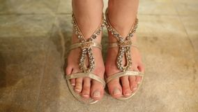女孩试穿在鞋店的凉鞋脚 免版税库存照片