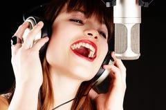 女孩话筒唱歌工作室 免版税库存照片