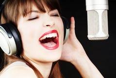 女孩话筒唱歌工作室 免版税库存图片