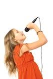 女孩话筒唱歌 免版税库存图片