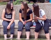 女孩说闲话和谈话与放松在水中的腿 免版税库存照片