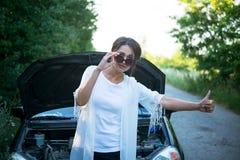 女孩请求帮忙在一辆残破的汽车附近 图库摄影