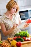女孩读一个菜谱 免版税库存图片
