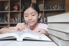 女孩读书和文字在学校图书馆里  免版税库存照片