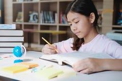 女孩读书和文字在学校图书馆里  免版税库存图片