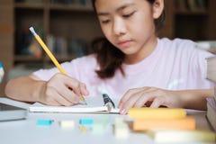 女孩读书和文字在学校图书馆里  图库摄影