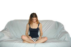 女孩读取沙发 免版税库存照片
