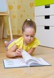 女孩读取配件箱在家 免版税库存图片