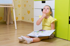女孩读取配件箱在家 图库摄影
