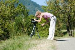 女孩调查在一个三脚架的照相机在绿色树和山背景在一个晴朗的夏日 库存图片