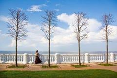 江边的女孩在Peterhof 免版税库存图片