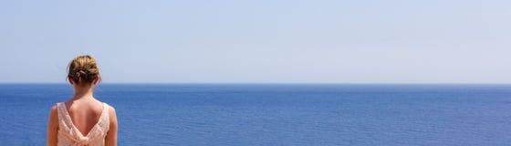 女孩调查在海的距离在一个温暖的夏日,文本的空间 库存图片