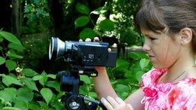 女孩调查在绿色公园背景背景的摄象机  影视素材