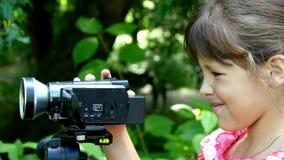 女孩调查在绿色公园背景背景的摄象机  股票录像