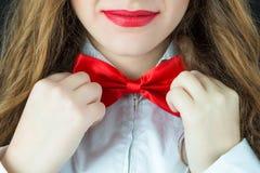 女孩调整一个红色蝶形领结在脖子 库存图片
