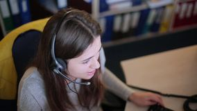 女孩谈话与一个客户在电话中心 股票录像