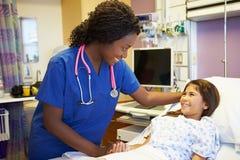 女孩谈话与女性护士在医房 免版税库存照片