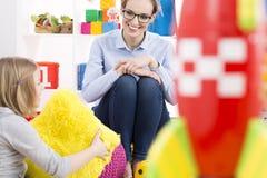 女孩谈话与心理学家 免版税库存照片