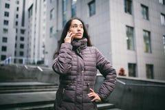 女孩谈话在手机在庭院商业中心 有长的黑发的女孩在冬天夹克穿戴了  免版税库存照片