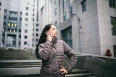 女孩谈话在手机在庭院商业中心 有长的黑发的女孩在冬天夹克穿戴了  免版税库存图片