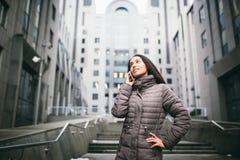 女孩谈话在手机在庭院商业中心 有长的黑发的女孩在冷气候的冬天夹克穿戴了 库存照片
