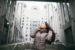 女孩谈话在手机在庭院商业中心 有长的黑发的女孩在冷气候的冬天夹克穿戴了 免版税库存图片
