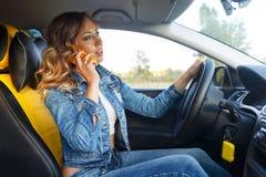 女孩谈话在汽车的电话 免版税库存照片