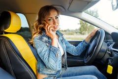 女孩谈话在汽车的电话 免版税库存图片