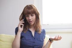女孩谈话在电话和惊奇 免版税库存图片
