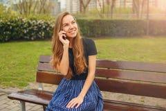 女孩谈话在电话户外 免版税库存图片