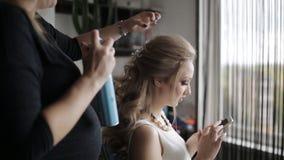 女孩谈话在电话,当化妆师为可爱的女孩美好的构成时做,美发师做发型 股票视频