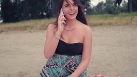 女孩谈话在电话,当坐海滩时 股票录像