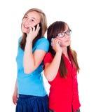 女孩谈话在他们的手机 图库摄影