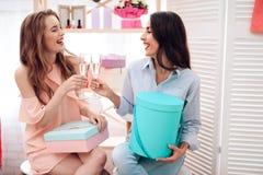 女孩购物 两个女孩获得乐趣在陈列室 他们拿着玻璃用香槟 免版税图库摄影