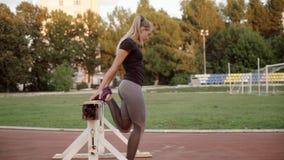 女孩赛跑者warmes在训练前的体育场内 女孩在一条腿蹲 影视素材