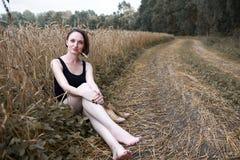 女孩赤足坐地面路在小麦夏天的领域、概念和旅行附近 免版税库存图片